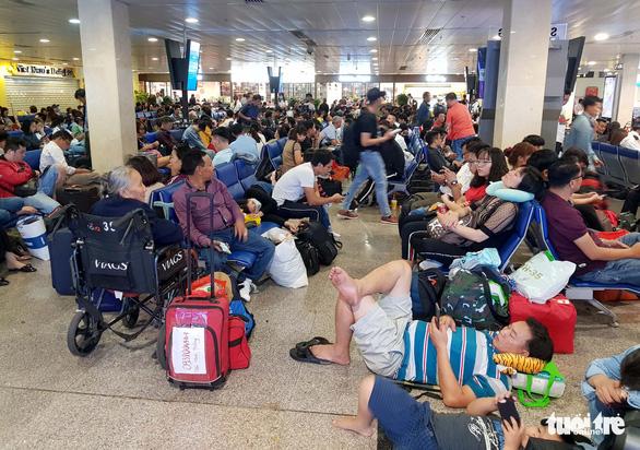 Máy bay liên tục hoãn chuyến, hành khách nằm, ngồi la liệt ở Tân Sơn Nhất - Ảnh 3.