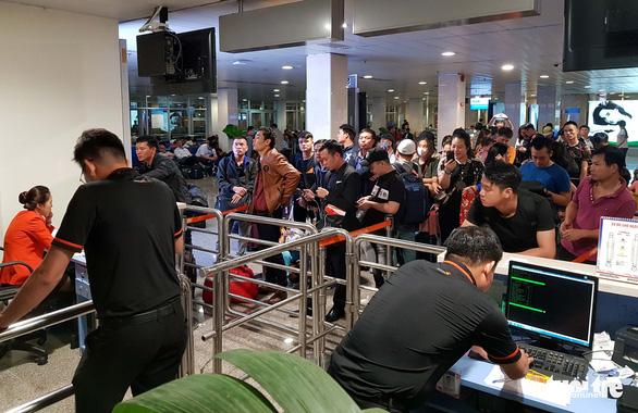 Máy bay liên tục hoãn chuyến, hành khách nằm, ngồi la liệt ở Tân Sơn Nhất - Ảnh 7.